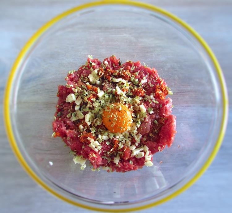 Carne picada numa taça de vidro temperada com sal, pimenta, chouriço picado, noz-moscada, orégãos, três dentes de alho picados, uma gema de ovo e vinho do Porto