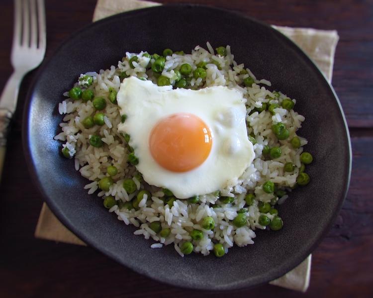 Arroz de ervilhas com ovos escalfados num prato