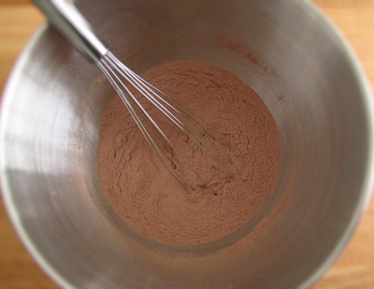 Açúcar, farinha, fermento, chocolate em pó e sal misturados numa taça grande