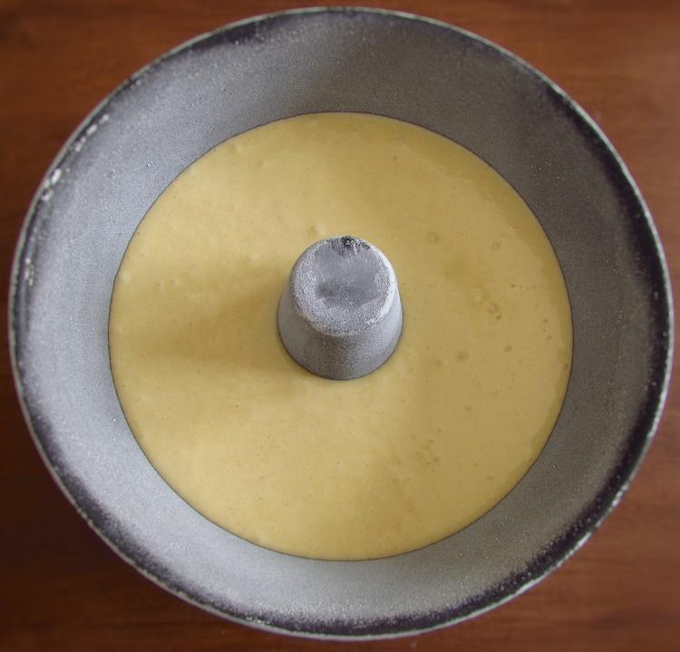 Massa de bolo de ouro numa forma de bolos redonda com furo no meio