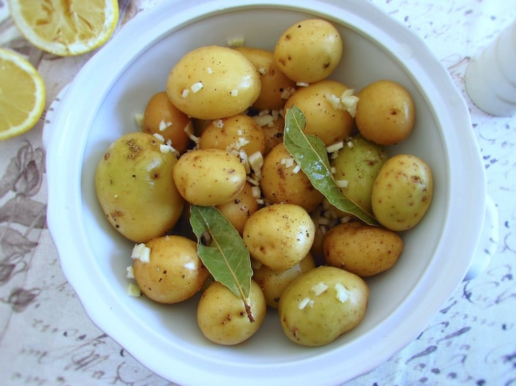 Potatoes seasoned with white wine, salt, pepper, chopped garlic, bay leaf and juice of one lemon on a tureen