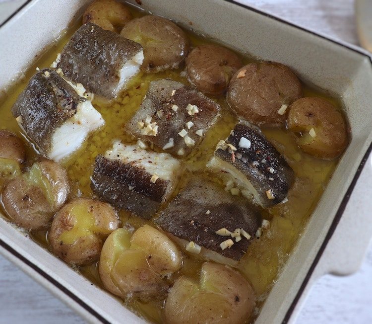 "Cod in the oven with ""punched"" potatoes on a baking dish"