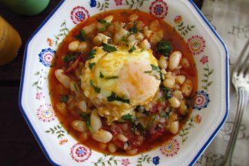 Feijão branco com chouriço e ovos escalfados numa tigela