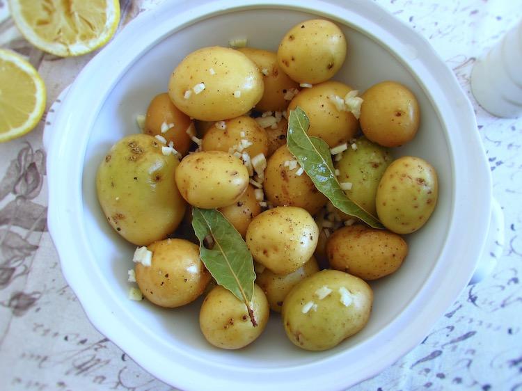Batatas temperadas com vinho branco, sal, pimenta, dentes de alho picados, louro e sumo de um limão numa terrina
