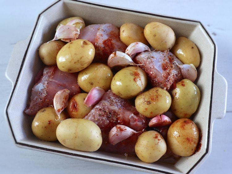 Rabbit with potatoes seasoned with salt, garlic, pepper, paprika and olive oil on a baking dish