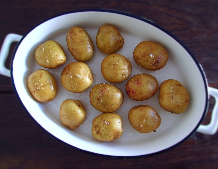 Potatoes seasoned with salt on a baking dish