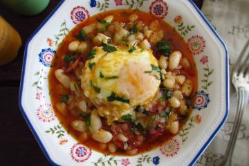White beans with chouriço and poached egg on a dish bowl