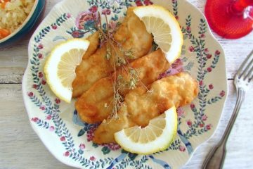 Fish fillets with lemon slices on a plate
