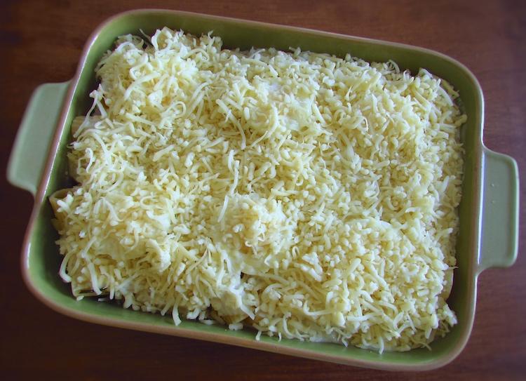 Massa, salsicha, rodelas de ovo, natas, béchamel e queijo ralado numa assadeira