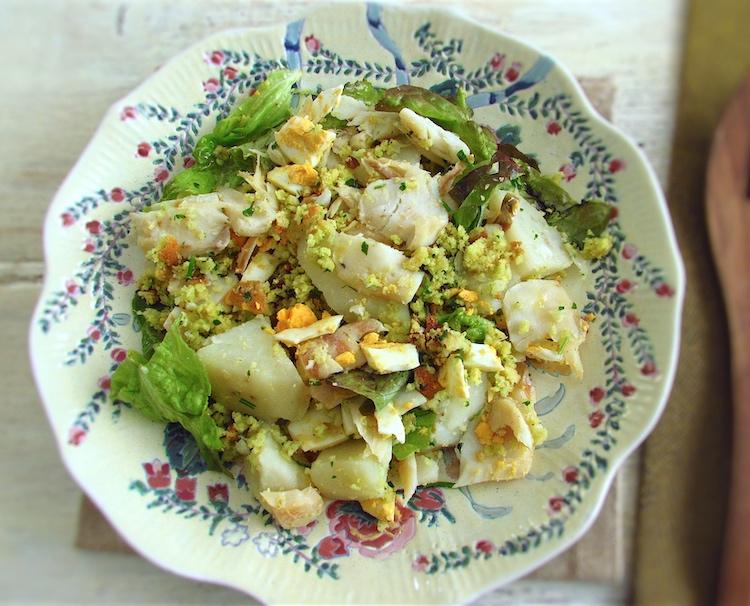 Salada de bacalhau com broa de milho num prato