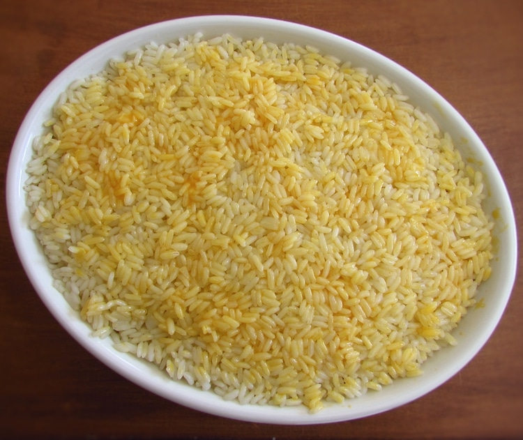 Duas camadas de arroz e uma camada de carne picada pincelada com gema de ovo batida numa assadeira