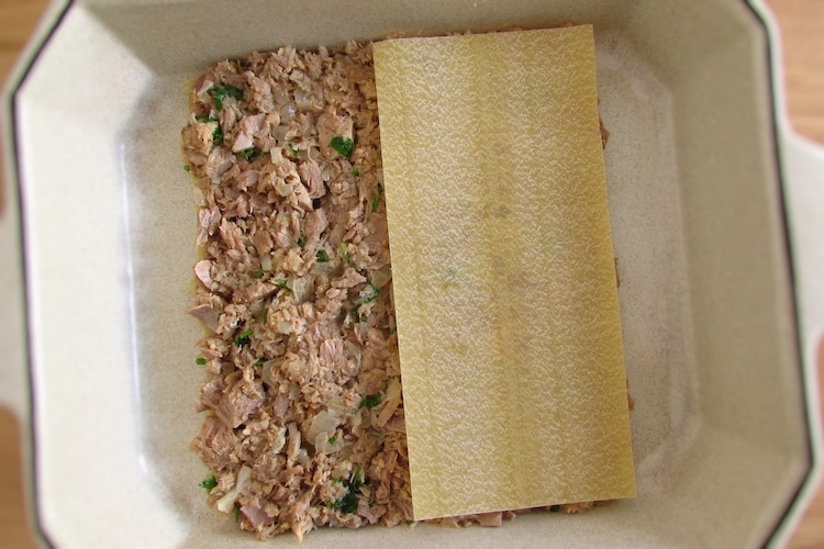 Mistura de atum e folhas de lasanha numa assadeira