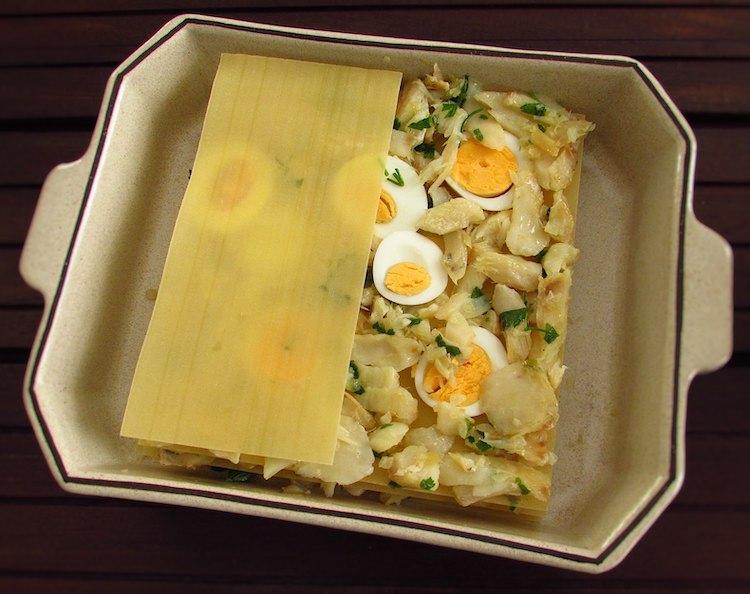 Folhas de lasanha, bacalhau e ovo numa assadeira
