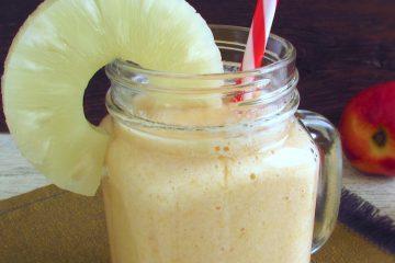 Peach and pineapple milkshake on a glass mug