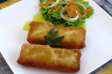 Breaded hake loins with salad on a plate
