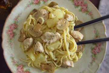 Chicken with spaghetti, pineapple and mushrooms on a plate