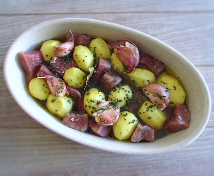 Batatas e cubos de vitela temperados com sal, pimenta, louro, alhos com casca esmagados, mel, azeite e alecrim picado numa assadeira