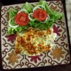 Fish fillets au gratin in the oven with salad on a plate
