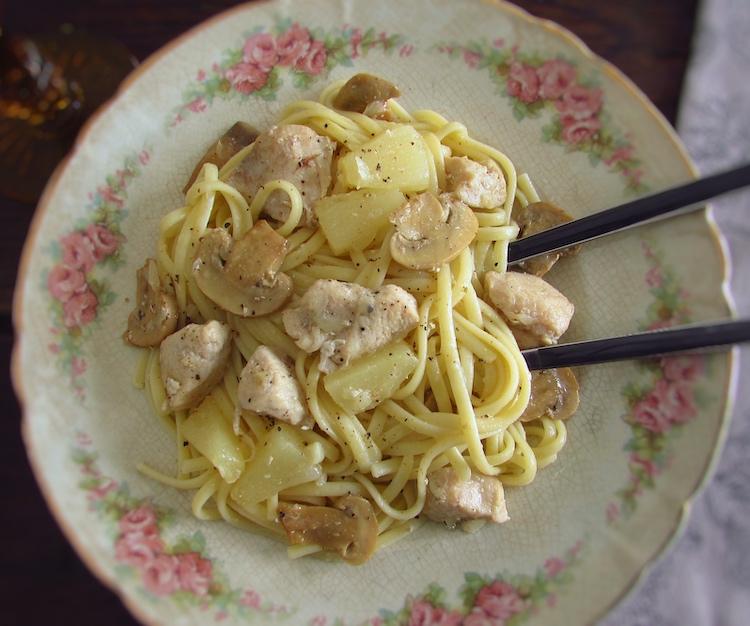 Frango com esparguete, ananás e cogumelos num prato