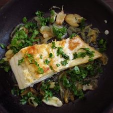 Fried cod with onion on a frying pan