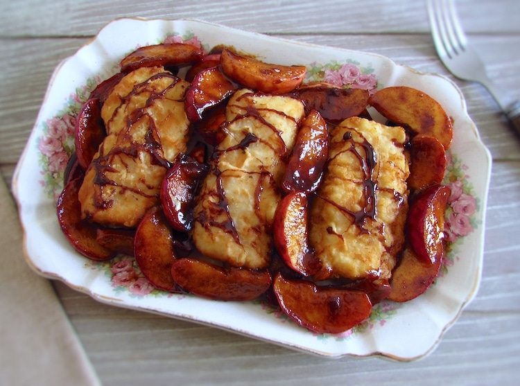Fried hake loins with caramelized apple on a platter