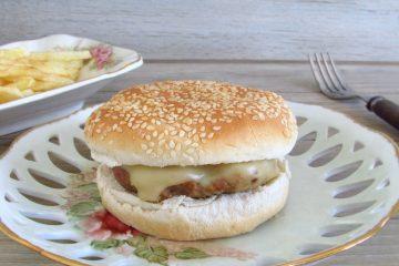 Hambúrgueres simples num prato com pão e queijo