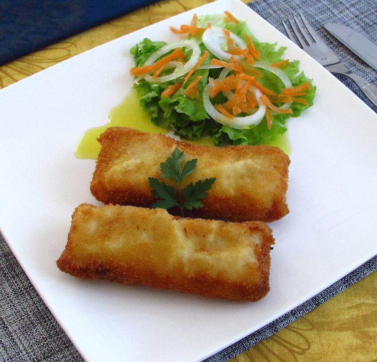Lombos de pescada panados com salada num prato