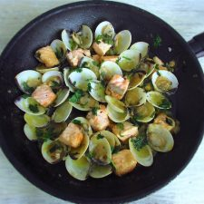 Salmon with clams on a frying pan