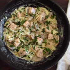 Salmon with cream and mushrooms on a frying pan