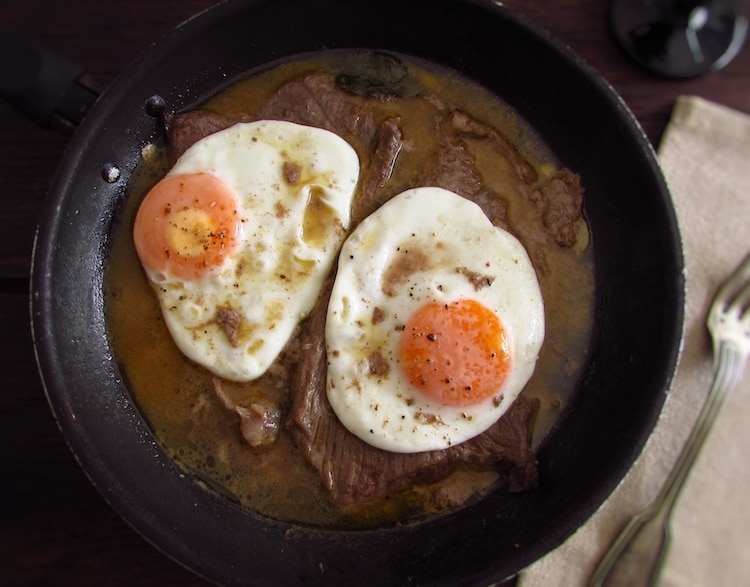 Veal steak with egg on a frying pan
