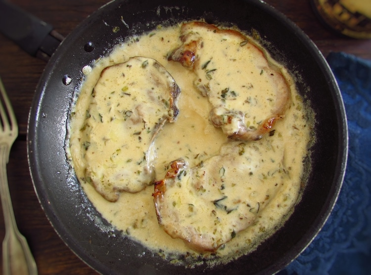 Chops with béchamel sauce on a frying pan