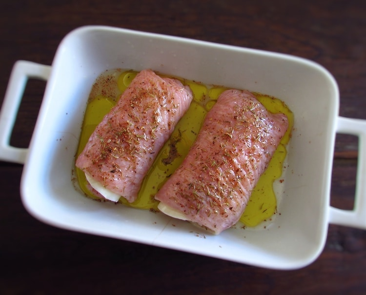 Stuffed turkey steaks drizzled with olive oil on a baking dish