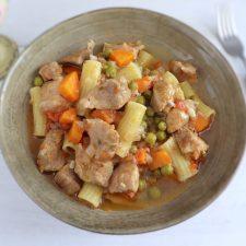 Carne de porco guisada com ervilhas, cenoura e massa num prato fundo