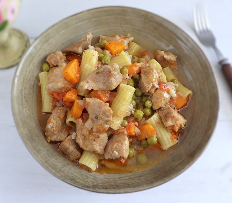 Pork stew with peas, carrot and pasta on a dish bowl