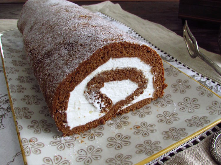 Chocolate roll cake filled with whipped cream on a platter