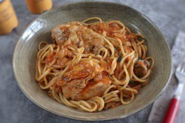 Frango guisado com esparguete num prato fundo