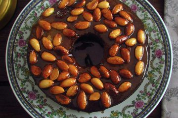 Banana cake topped with caramelized almond on a plate