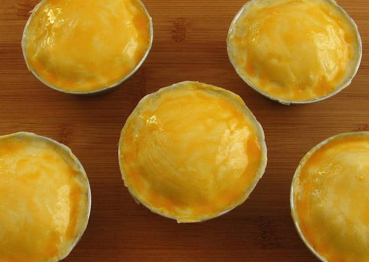 Mini chicken pies brushed with beaten egg yolk
