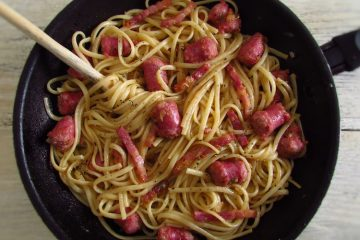 Spaghetti with fresh sausage and bacon on a frying pan