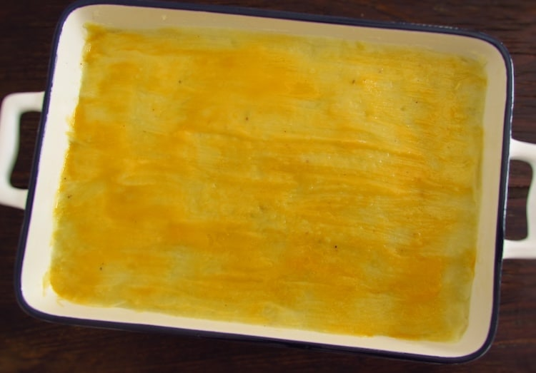 Fish and puree brushed with beaten egg yolk on a baking dish