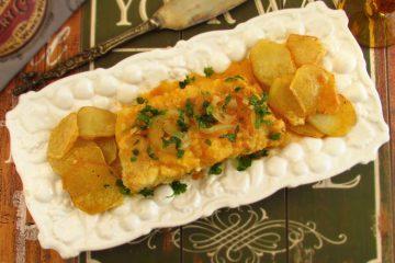 Bacalhau frito com molho de tomate numa travessa