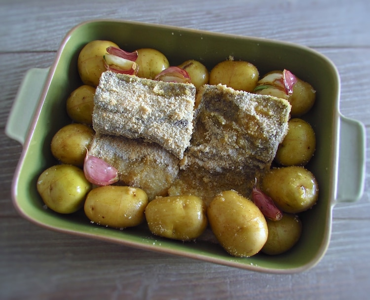 Potatoes and cod drizzled with olive oil mixture on a baking dish