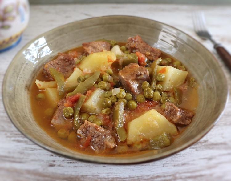 Carne estufada com batatas e ervilhas num prato fundo