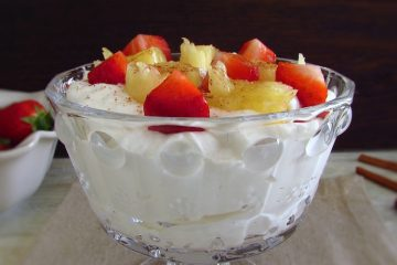 Chantilly with strawberries and pineapple on a glass bowl