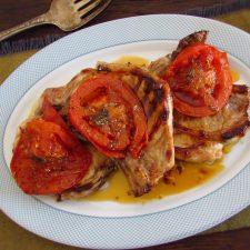 Costeletas de porco grelhadas com tomate numa travessa
