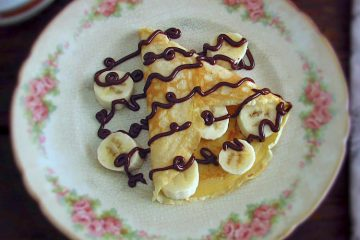 Crepe with banana and chocolate on a plate