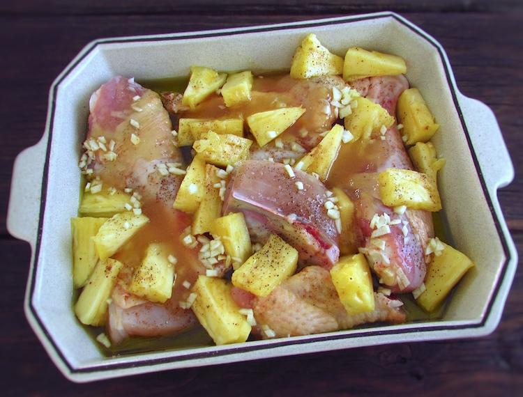 Frango com ananás temperado com sal, pimenta, noz-moscada, alhos picados, mel e azeite numa assadeira