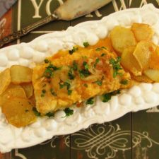 Fried cod with tomato sauce on a platter
