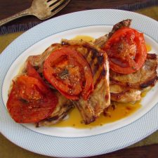 Pork chops grilled with tomato on a platter