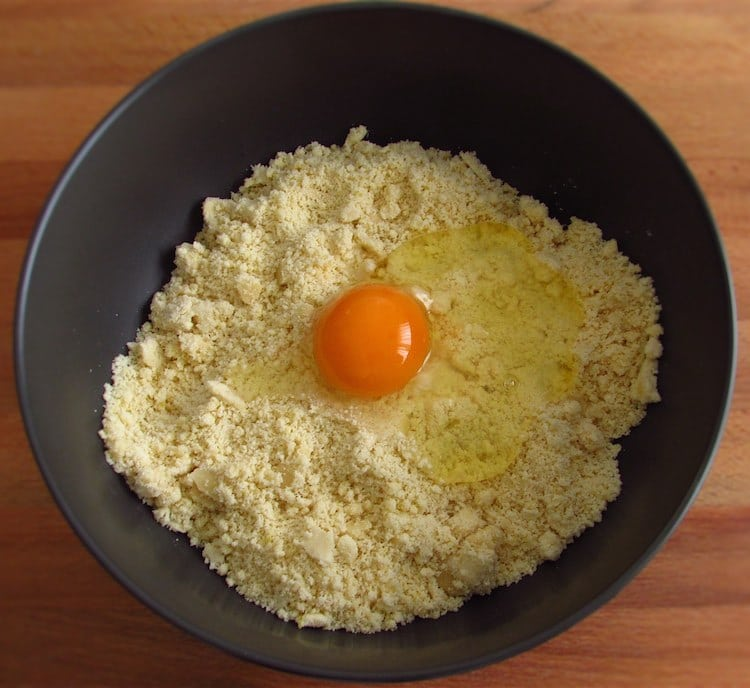 Mistura de farinha e açúcar com um ovo numa taça